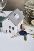 Photo house model on white table with keys and moneybox, real estate concept
