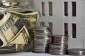 vista da vicino del modello di casa vicino monete dargento e banconote in dollari in moneybox, concetto immobiliare