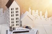 domy na bílém dřevěném stole s kontraktem, mincemi a klíči v blízkosti bílého papíru, koncepce nemovitostí