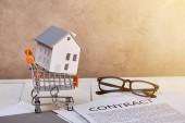 model domu v malém nákupním vozíku na bílém dřevěném stole se zakázkou a sklenicemi na slunci, koncepce nemovitostí