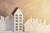 houses models on white wooden table near white paper cut city in sunlight, real estate concept