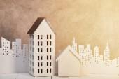 domy na bílém dřevěném stole v blízkosti bílého papíru, střih města na slunci, koncepce nemovitostí