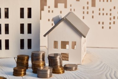houses models on white wooden table with coins, real estate concept