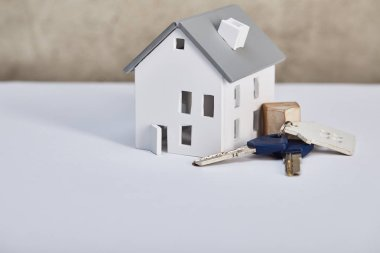 house model on white table with keys near grey textured wall, real estate concept
