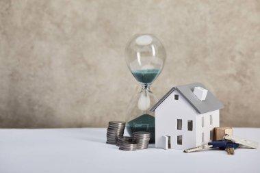 kum saati, sikke ve anahtarlar, gayrimenkul kavramı ile beyaz masa üzerinde ev modeli