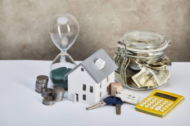 house model with hourglass, calculator, money and keys, real estate concept