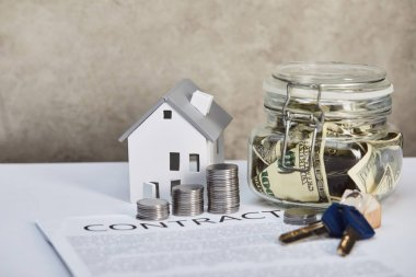house model on white table with silver coins, keys, contract and moneybox on grey background, real estate concept