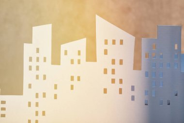 white paper cut houses in sunlight, real estate concept