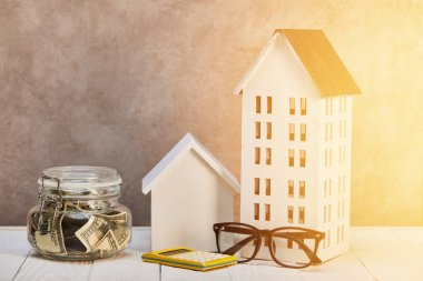 Houses models on white wooden table with glasses, calculator and moneybox in sunshine, real estate concept stock vector