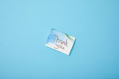 Greeting card with thank you lettering on blue background with copy space stock vector