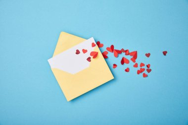 Yellow envelope with blank white card and paper cut hearts on blue background stock vector