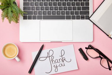 Top view of laptop, green plant, coffee, notebook, glasses and card with thank you lettering at workplace on pink background stock vector