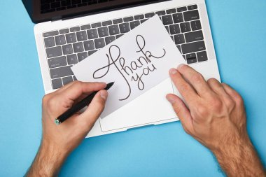Cropped view of man writing on card with thank you lettering near laptop on blue background stock vector