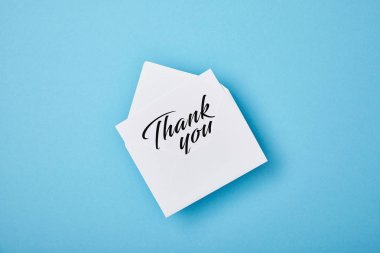 Envelope with thank you lettering on white card on blue background stock vector