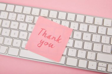 Top view of pink sticky note with thank you words on laptop keyboard on pink background stock vector