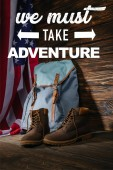 Photo trekking boots, backpack and american flag on wooden surface with we must take adventure illustration