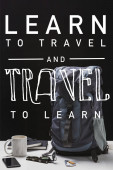 backpack, cup, notebooks, smartphone and trekking equipment isolated on black with learn to travel and travel to learn illustration