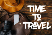 top view of brown leather bag, hat, digital camera and smartphone on wooden table with time to travel illustration