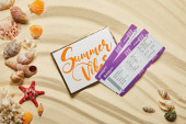 top view of card with summer vibes letting near air tickets and seashells on sandy beach