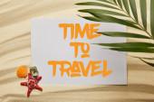 felülnézet zöld pálmalevél közel plakát az idő az utazási betűk, tengeri csillag és a tengeri kagylókból a homokos tengerparton