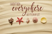 flat lay of seashells and red starfish on sandy beach in summertime with I have not been everywhere, but it is on my list letting