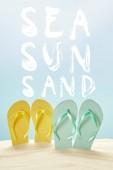letní žluté a modré žabky ve zlatém písku izolovanému na modrém moři, sluncem a žlutým písmem