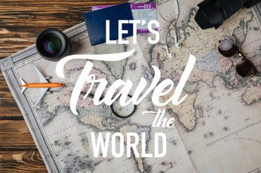 top view of magnifying glass, small model plane, sunglasses, photo camera, lens and passport with boarding pass on map with lets travel the world illustration