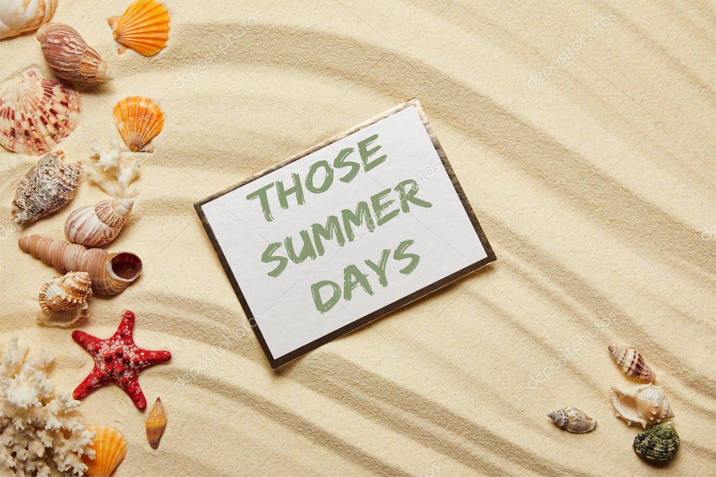 Top view of card with those summer days lettering near seashells, red starfish and corals on sandy beach
