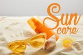 sárga stílusos napszemüveg és fényvédő narancssárga palackon homokkal a kagyló szürke háttér napellátás betűkkel