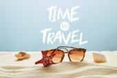 hnědé, stylové sluneční brýle na písku s mušlemi a hvězdicemi na modrém pozadí s časem k cestování s písmem