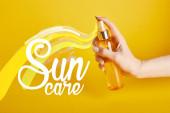 nyírt kilátás a nő gazdaság palack fényvédő spray, sárga háttér nap ellátás betűkkel