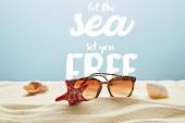 barna stílusos napszemüveg a homok tengeri kagylókból és tengeri csillag a kék háttér hagyja, hogy a tenger meg ingyenes betűkkel