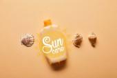 kilátás a tengeri kagylókból és palackból napbarnító krém bézs háttérrel a napellátás betűkkel