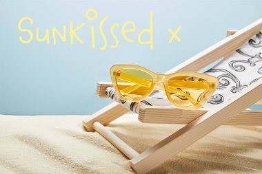 yellow stylish sunglasses on deck chair on sand on blue background with sun-kissed lettering