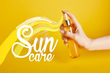 cropped view of woman holding bottle with sunscreen spray on yellow background with sun care lettering