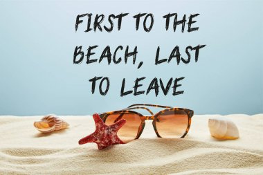 Brown stylish sunglasses on sand with seashells and starfish on blue background with first to the beach, last to leave lettering stock vector