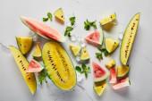 Ansicht von geschnitten köstlichen exotischen gelben und roten Wassermelonen mit Eis und Minze auf Marmoroberfläche
