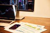 Fotografie notebook a počítač s grafy, grafy, dokumenty a smartphone na stole