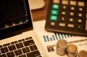 Fotografie selektivní zaměření laptopu, mincí, papírů a kalkulačky na stůl