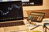 notebook s grafy, mincemi, papíry, perem, sklenicemi a kalkulačkou