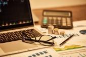 selektivní zaměření notebooku, mincí, papírů, brýlí, pera a kalkulačky na stůl