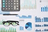 a lapok, a toll, a számológép és a szemüvegek felülnézete az asztalon