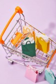 decorative shopping cart with colorful paper bags on violet background