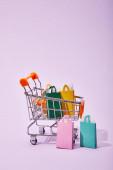 Fotografie vozík s hračkami s barevným papírem nákupní tašky na fialovém pozadí