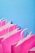 Pink papír bevásárló táskák, fehér fogantyúval, kék háttér