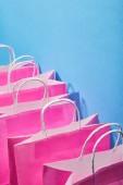 Růžové nákupní tašky s bílými úchyty na modrém pozadí