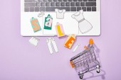 top view of colorful toy bags with sale lettering and paper cut of clothes on laptop falling in toy shopping cart on violet