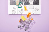 top view of small paper bags with sale lettering and paper cut of clothes on laptop falling in toy shopping cart on violet