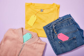 top view of colorful paper tags on clothes on violet