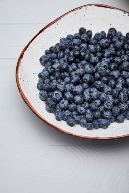 plate with delicious blueberries on white wooden table